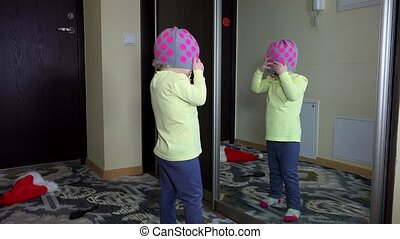 Little cute child girl simper in front of mirror at home