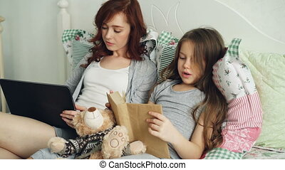 Little cute daughter reading text book doing homework for elementary school while her loving mother browsing and working on digital tablet sitting together on cozy bed at home