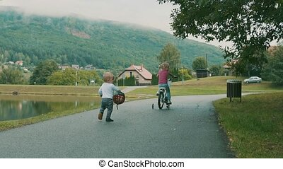 Little cute girl and her younger brother in the nature by...