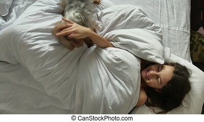 Little cute girl and indoors dog sleeping in bed. little...