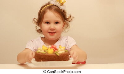 Little cute girl and on birthday cake at party. Funny happy child. Dessert for children