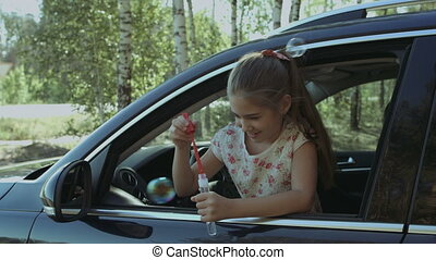 Little cute girl blowing soap bubbles in the car