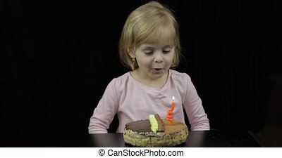Little cute girl blows out festive candle on birthday cake...