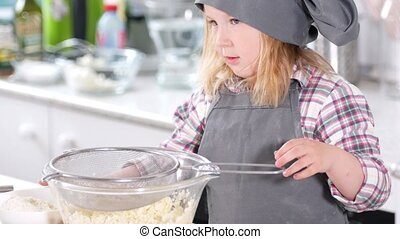 Little cute girl chef preparing to sift flour through a...