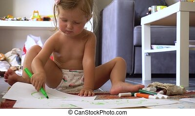 Little cute girl drawing on paper sitting in living room at...