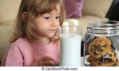 Little cute girl eating cookie