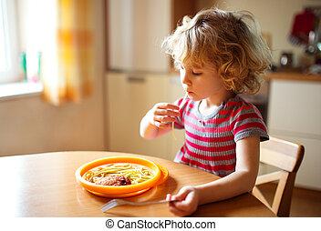 Little cute girl eating spaghetti