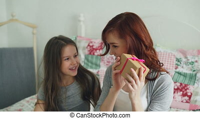Little cute girl giving gift box to her young happy mom celebrating mothers day sitting on bed in cozy bedroom at home