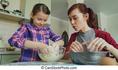 Little cute girl helping her mother in the kitchen stirring...