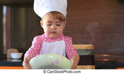 little cute girl in chef suit playing with the dishes in the kitchen