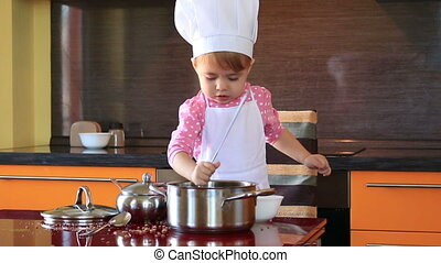 little cute girl in chef suit playing in the kitchen with a...
