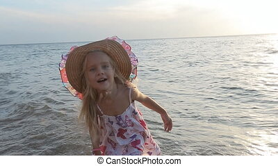Little cute blond girl in sundress and straw hat standing knee-deep in sea water