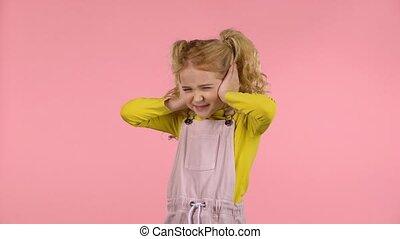 Little cute girl is covering her ears in studio - Little...