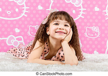 Little cute girl is on the fur carpet on pink background