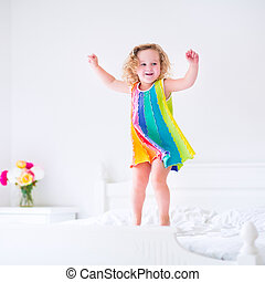 Little cute girl jumping on a bed - Cute little curly ...
