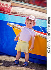 Little cute girl leaning on a colourful wooden boat