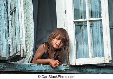 Little cute girl looks out the window house in the village.