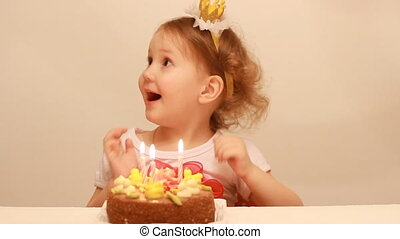 Little cute girl makes a wish and blows out candles on birthday cake at party. Funny happy child. The concept of a children's holiday. 3 years.