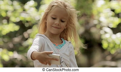 Little cute girl making selfie on the phone in the green forest