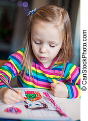 Little cute girl painting with pencils while sitting at her table