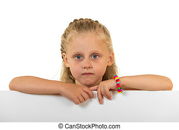 Little cute girl peeks out from behind the banner, isolated on white