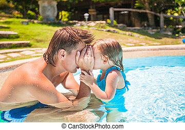 Little cute girl play with father at the pool in tropical hotel