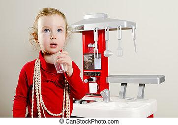Little cute girl playing in children's kitchen.