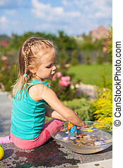 Little cute girl playing with toys in the yard
