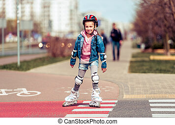 little cute girl riding on roller skates