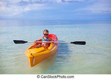 Little cute girl rowing a boat in blue clear sea