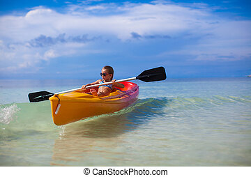 little cute girl rowing a boat in clear sea