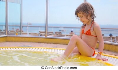 girl sits in swimming pool and splashes water - little cute...