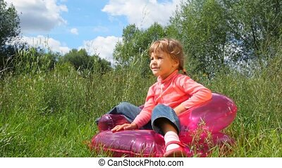 little cute girl sits on inflatable chair outdoors in summer park