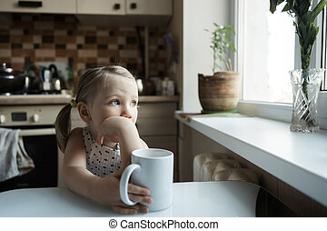 Little cute girl sitting at the table in the kitchen