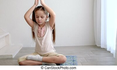 little cute girl sitting in yoga lotus pose and meditates...