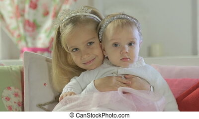 Little cute girl sitting on couch and hugging her little sister