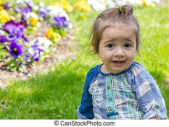 little cute girl sitting on the grass