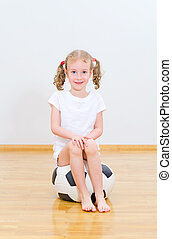 Little cute girl sitting on the soft ball.