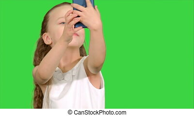 Little cute girl smile and taking selfie on a Green Screen, Chroma Key