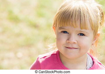 little cute girl smiles and looks into the camera in a city park