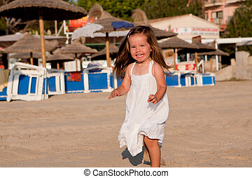 little cute girl smiling playing on beach in summer