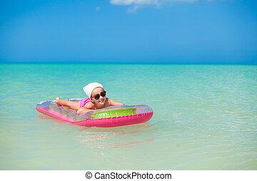Little cute girl sunbathing on pink air-bed in warm sea