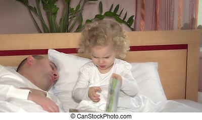 Little cute girl wake up her father sleeping and embrace hug in bed