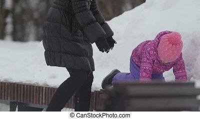Little cute girl walking in the snow and falling into the snowbank for a walk with her mom