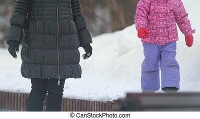 Little cute girl walking in the snow for a walk with her mom