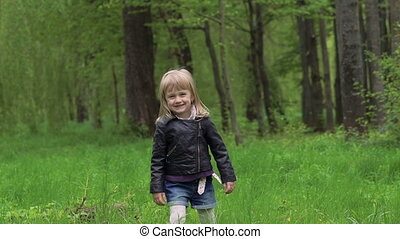 Little cute girl walking on a grass and smiling. Slowly