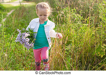 Little cute girl walking with a bouquet of flowers