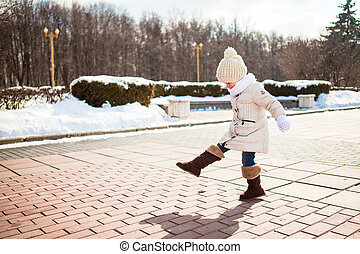 Little cute girl walks in the winter on a sunny day outdoors