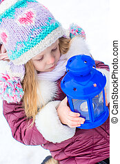 Little cute girl warms her hands on candle in blue lantern in winter time