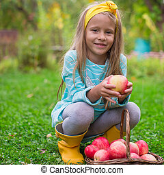 Little cute girl with basket of apples in autumn